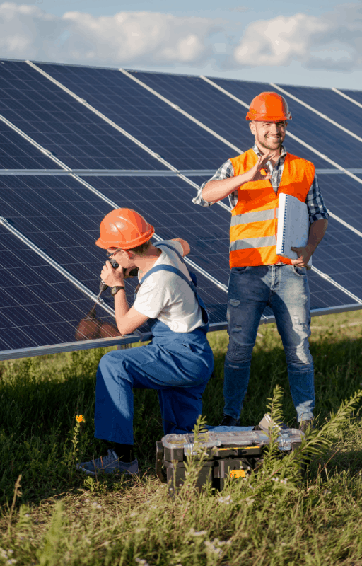 two men working on a solar panel in a field